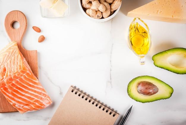 Concetto di dieta chetogenica a basso contenuto di carboidrati. alimento sano ed equilibrato con alto contenuto di grassi sani. dieta per cuore e vasi sanguigni. blocco note bianco del fondo degli ingredienti organici