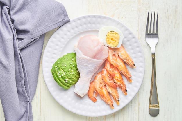 Concetto di dieta chetogenica. un set di prodotti per la dieta cheto a basso contenuto di carboidrati. avocado verde, sesamo, coscia di pollo, uova e gamberi. concetto di cibo sano.