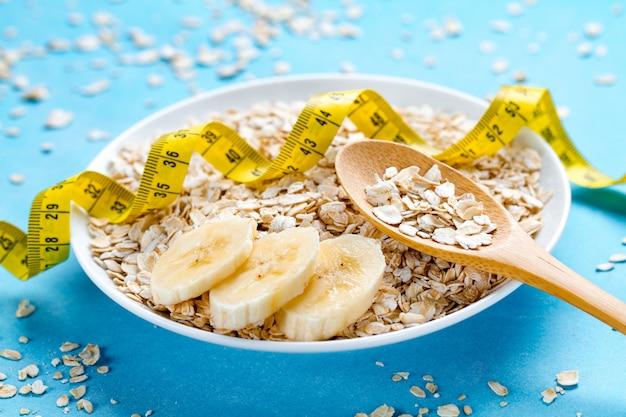 Concetto di dieta. ciotola e cucchiaio di farina d'avena con la banana matura fresca e nastro adesivo di misurazione giallo su fondo blu