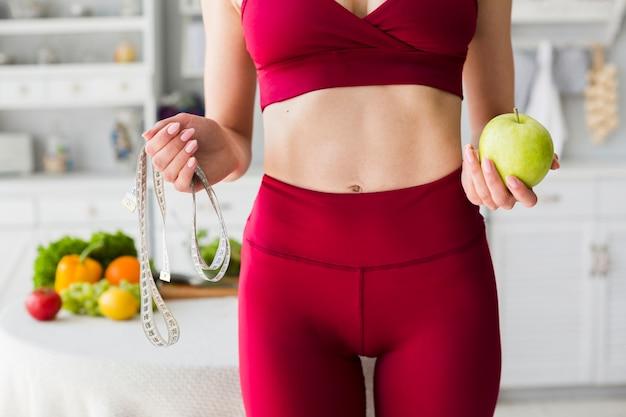 Concetto di dieta con donna sportiva in cucina