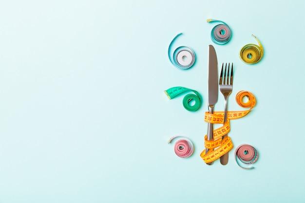 Concetto di dieta con forchetta e coltello circondato con nastri di misurazione colorati su blu