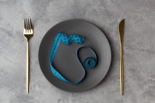 Concetto di dieta con un nastro di centimetro su un piatto con un coltello e una forchetta su uno sfondo grigio
