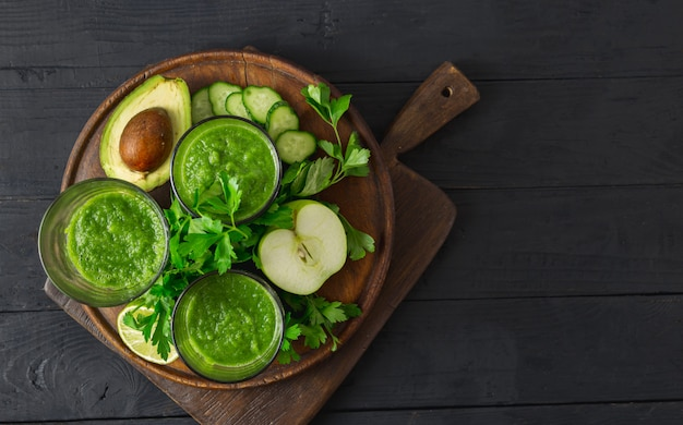 Concetto di dieta della disintossicazione, frullato verde su una vista superiore del fondo di legno