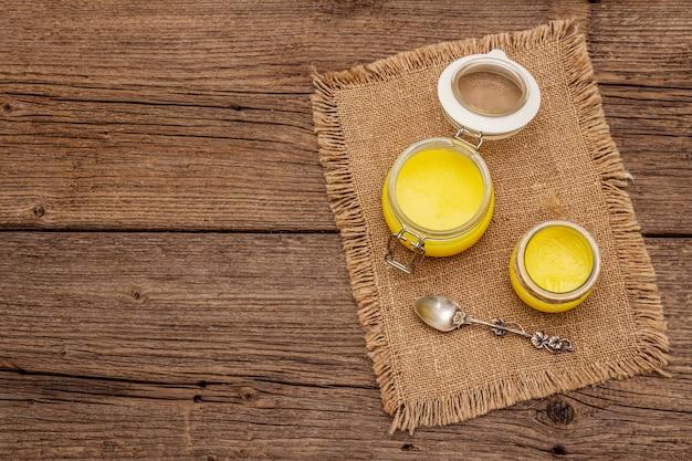 Concetto di dieta di grassi sani o piano di stile paleo. vaso di vetro, cucchiaio d'argento su tela di sacco vintage.