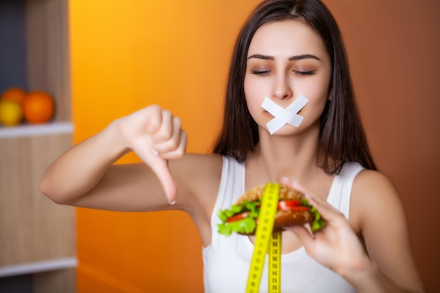 Concetto di dieta donna carina con la bocca sigillata mantiene hamburger grasso