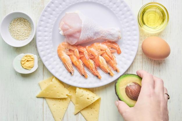 Concetto di dieta keto. alimenti dietetici chetogenici. sfondo alimentare bilanciato a basso contenuto di carboidrati. verdure, frutti di mare, pollo, formaggio, noci su