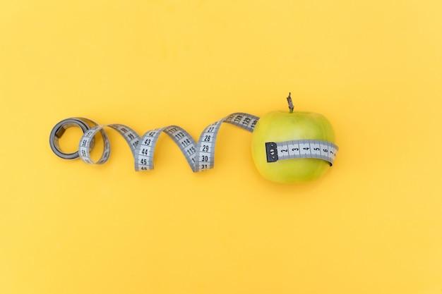 Concetto di dieta. misura di nastro e mela su sfondo giallo