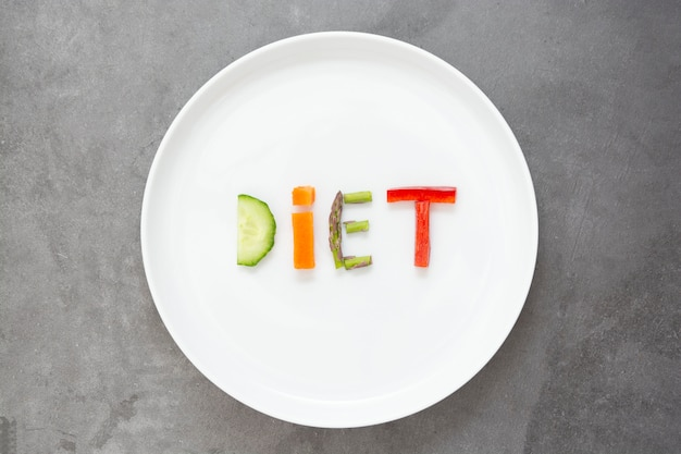 Concetto di dieta. piatto bianco con la parola - dieta - composto da fette di frutta e verdura diverse.