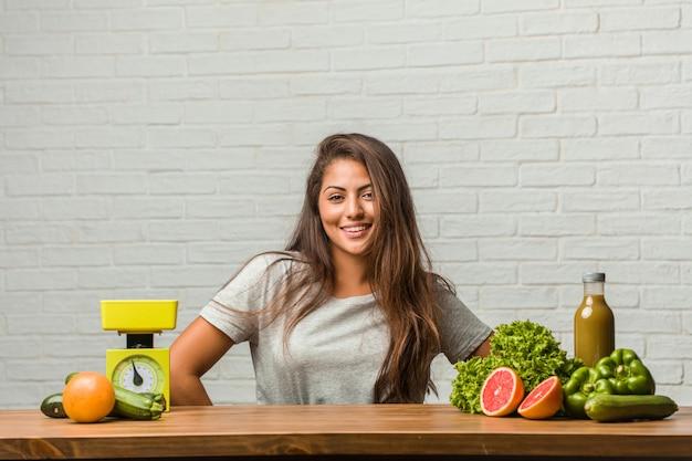 Concetto di dieta ritratto di una giovane donna latina con le mani sui fianchi, in piedi, rilassato e sorridente, molto positivo e allegro