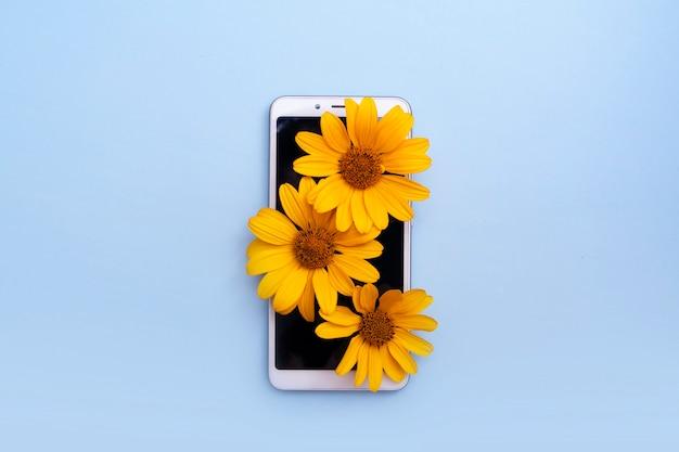 Concetto di disintossicazione digitale. fiori gialli su uno smartphone con copia spazio.