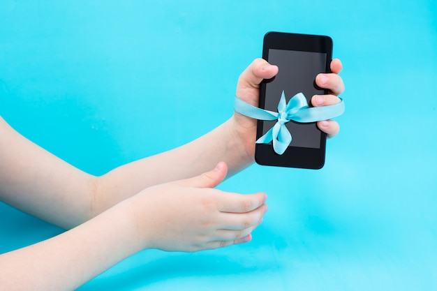 Concetto di disintossicazione digitale. la mano di un bambino con uno smartphone è legata con un nastro blu e una seconda mano li raggiunge. dipendenza da gadget