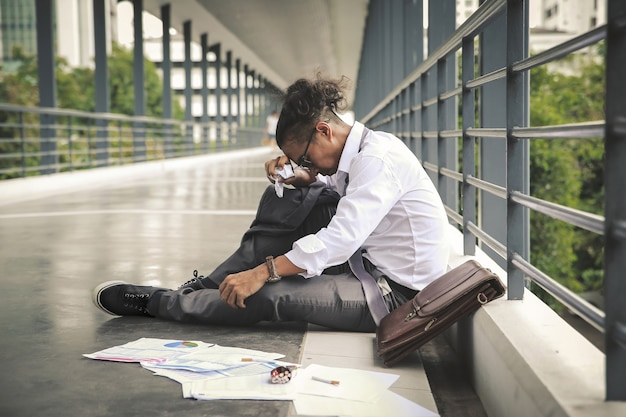 Concetto di disoccupazione, i disoccupati degli uomini d'affari della società siedono sul cavalcavia.