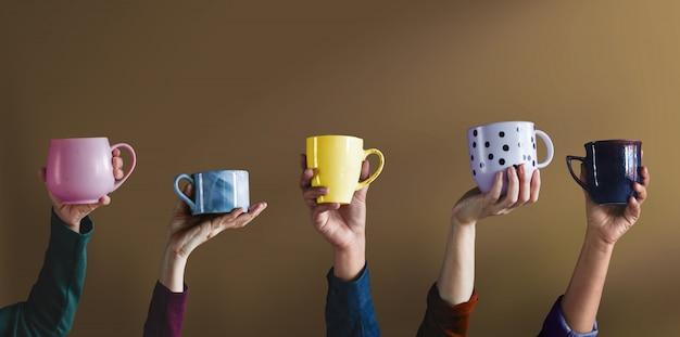 Concetto di diversità e stile di vita. le persone hanno alzato la mano per mostrare la propria tazza e le proprie bevande preferite