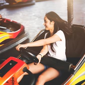 Concetto di divertimento di giro del parco di divertimenti della ragazza
