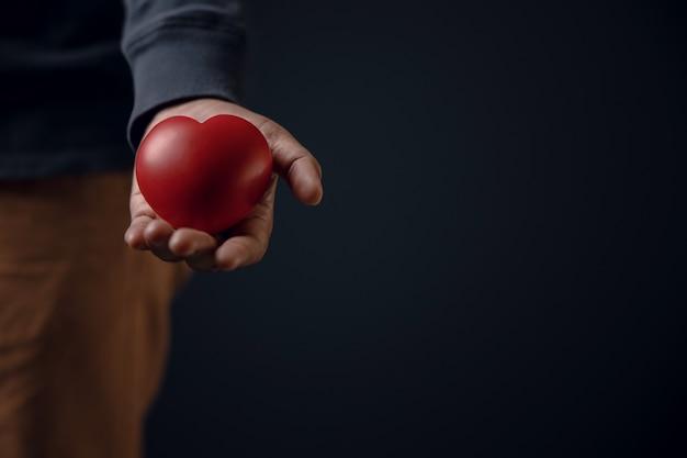 Concetto di donazione. confortevole mano aperta dal donatore che dà un cuore rosso a un destinatario.