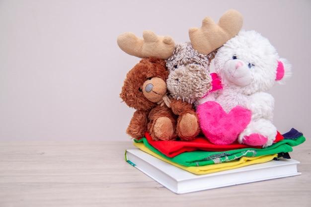 Concetto di donazione. dona una scatola con vestiti per bambini, libri, materiale scolastico e giocattoli. orsacchiotto con grande cuore rosa nelle mani.