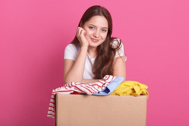 Concetto di donazione. la tenuta della donna dona la scatola con il pieno di vestiti, la femmina sorridente adorabile tiene la mano sotto il mento e i vestiti donano la scatola, signora che porta la maglietta bianca casuale, posare isolata sul rosa.
