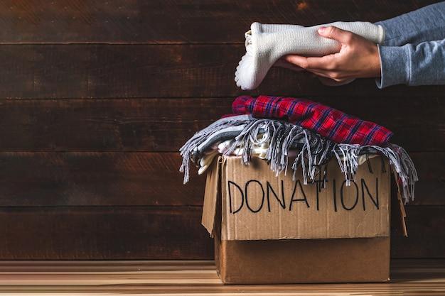Concetto di donazione. scatola di donazione con abiti di donazione. carità. aiutare le persone povere e bisognose