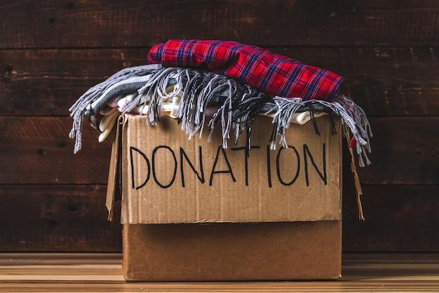 Concetto di donazione. scatola di donazione con abiti di donazione. carità. aiuto per le persone bisognose