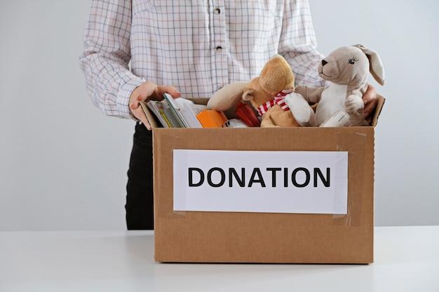 Concetto di donazione. uomo che tiene la scatola piena di libri e giocattoli. fai una donazione per i bambini, per favore