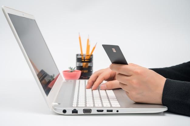 Concetto di e-commerce. la mano dell'uomo che tiene in mano una carta di credito e immette i dati su un computer portatile.