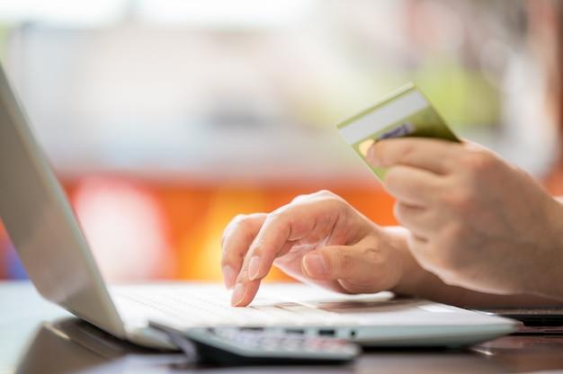 Concetto di e-commerce. mano d'uomo che tiene una carta di credito in mano e immissione dei dati su un laptop