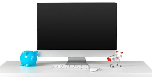 Concetto di e-commerce, schermo del monitor del computer sul tavolo con accessori per lo shopping