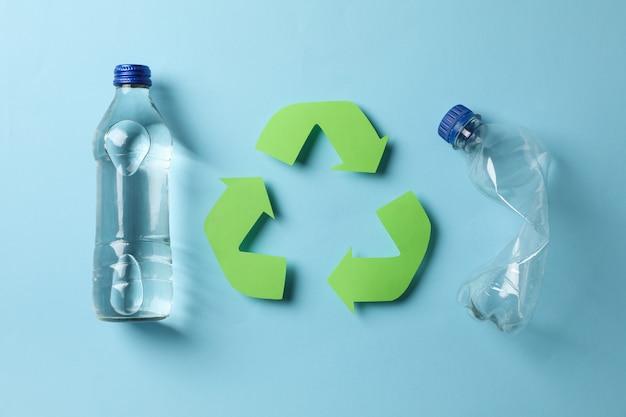 Concetto di eco con il riciclaggio del simbolo e bottiglie sul blu