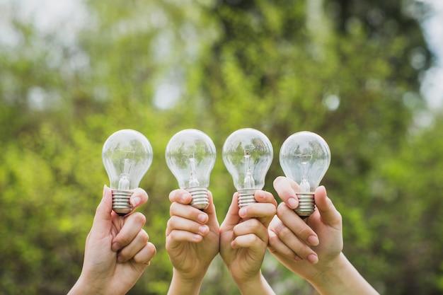 Concetto di eco con le mani che tengono le lampadine
