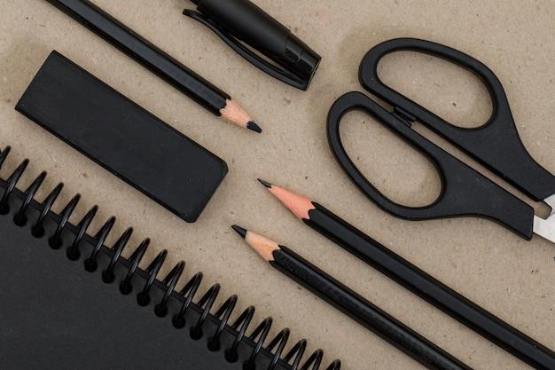 Concetto di educazione con matite, penna, forbici, taccuino, gomma su carta.
