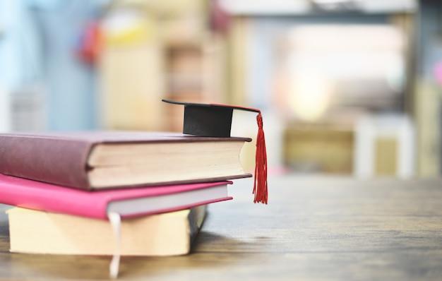 Concetto di educazione con tappo di laurea su un libro sul tavolo di legno