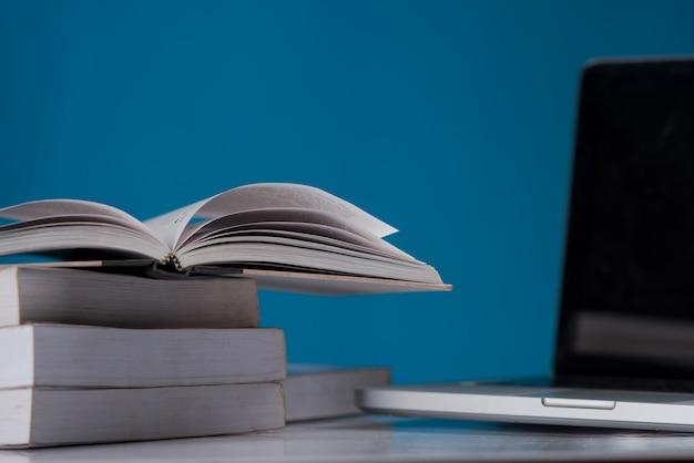 Concetto di educazione, libri e laptop in biblioteca