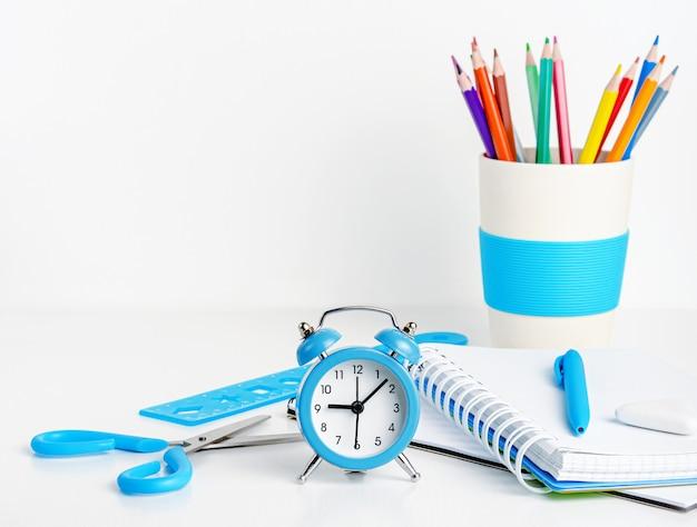 Concetto di educazione. rifornimenti di scuola e orologio blu su bianco. copia spazio