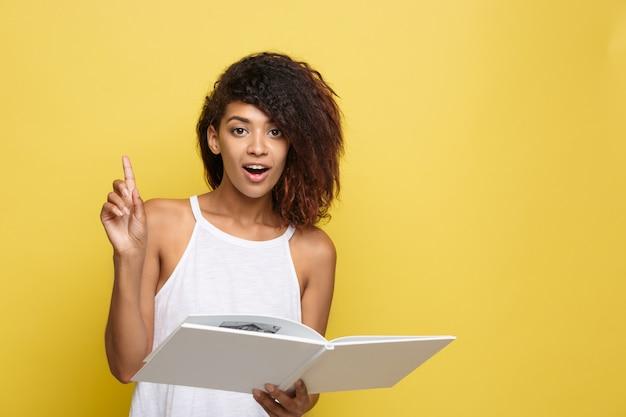 Concetto di educazione - ritratto di donna afroamericana che legge un libro. sfondo di studio giallo. copia spazio.