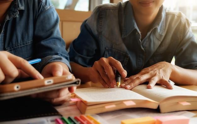 Concetto di educazione. studio studente e brainstorming campus concept. primo piano di studenti che discutono il loro tema su libri o libri di testo. messa a fuoco selettiva.
