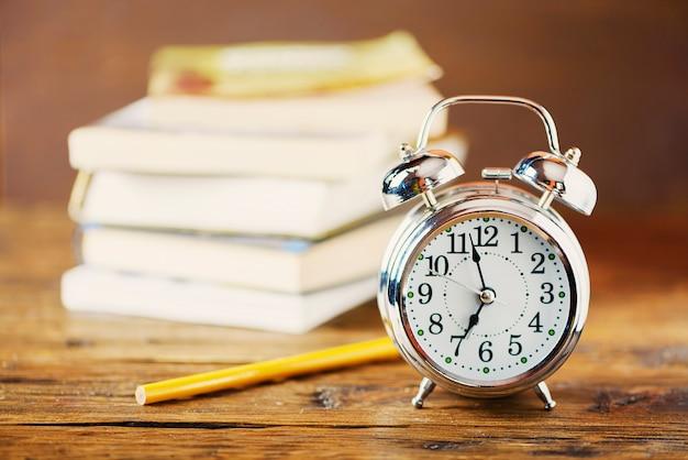 Concetto di educazione. sveglia e libri sulla tavola di legno, fuoco selettivo