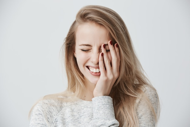 Concetto di emozioni positive. la bella donna bionda caucasica felice si è vestita casualmente sorridendo largamente, mostrando i suoi denti bianchi perfetti, rilassandosi, chiudendo gli occhi a causa della gioia, trascorrendo il fine settimana all'interno