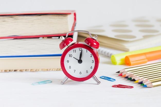 Concetto di esame sveglia rossa, libri, matite colorate. torna al concetto di scuola