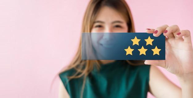 Concetto di esperienze del cliente. donna felice che sorride e mostra valutazione eccellente con cinque stelle