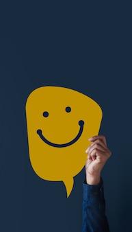 Concetto di esperienze del cliente. la gente moderna ha alzato la mano per dare un'icona faccia felice e una recensione positiva sulla carta. sondaggi sulla soddisfazione del cliente. vista frontale
