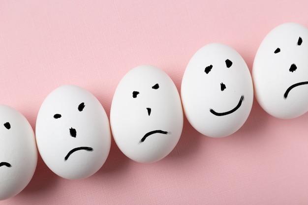 Concetto di essere unico. hapyy sorride su un uovo tra sorrisi tristi.