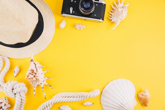Concetto di estate accessori da viaggio: un cappello di paglia, una macchina fotografica, una corda, conchiglie e occhiali da sole.