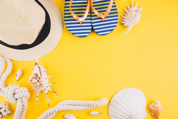 Concetto di estate accessori da viaggio: un cappello di paglia, una macchina fotografica, una corda, conchiglie e pantofole.