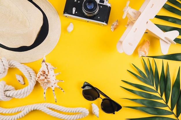 Concetto di estate accessori da viaggio: un cappello di paglia, una macchina fotografica, una corda, un aereo di legno, conchiglie, pantofole e occhiali da sole.