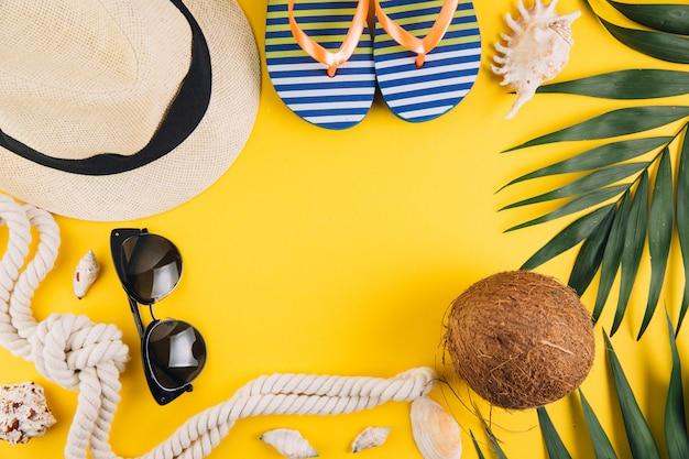 Concetto di estate accessori da viaggio: un cappello di paglia, una noce di cocco, un guscio di corda, pantofole e occhiali da sole.