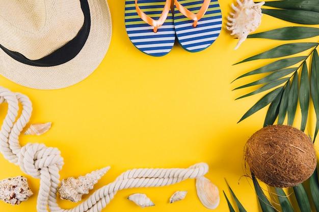 Concetto di estate accessori da viaggio: un cappello di paglia, una noce di cocco, una corda e conchiglie.