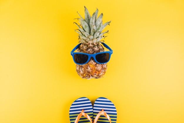 Concetto di estate ananas carino e divertente con occhiali da sole e infradito su sfondo giallo.