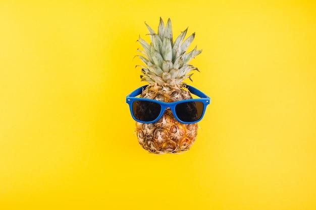Concetto di estate ananas carino e divertente con occhiali da sole su sfondo giallo.