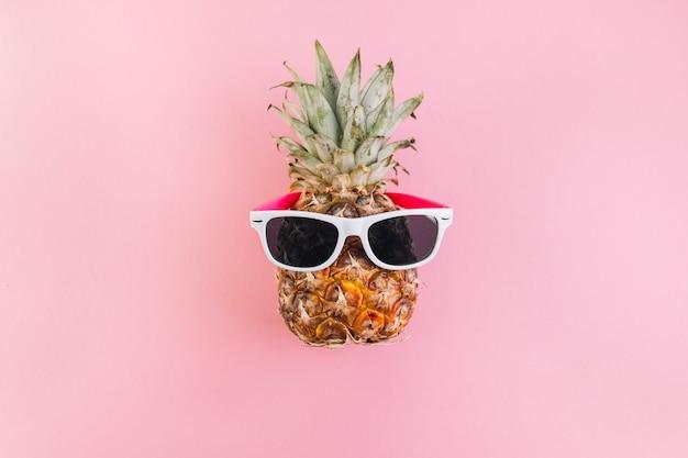 Concetto di estate ananas carino e divertente con occhiali da sole su sfondo rosa.