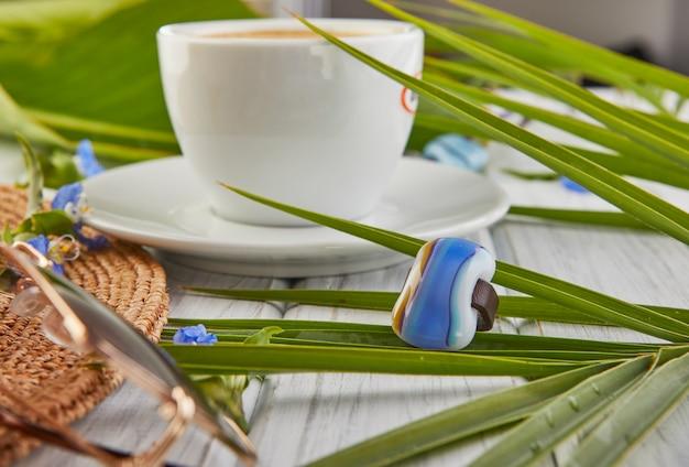 Concetto di estate con gioielli. caffè, cappello delle foglie di palma e vetri con un anello su un fondo di legno bianco